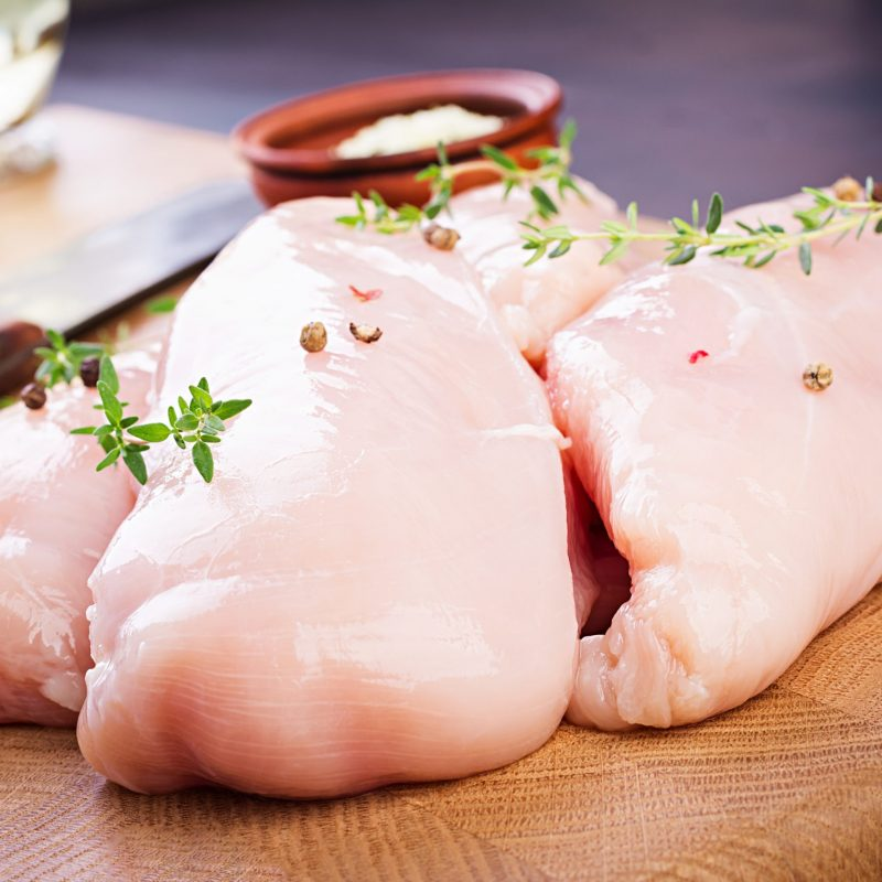 Raw chicken breast fillets on wooden cutting board with herbs and spices.
